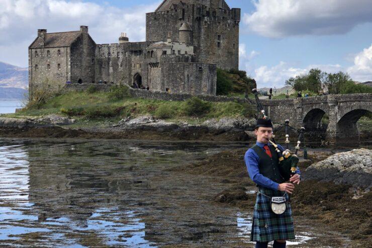 Scottish Bagpiper in front of Eilean Donan Castle